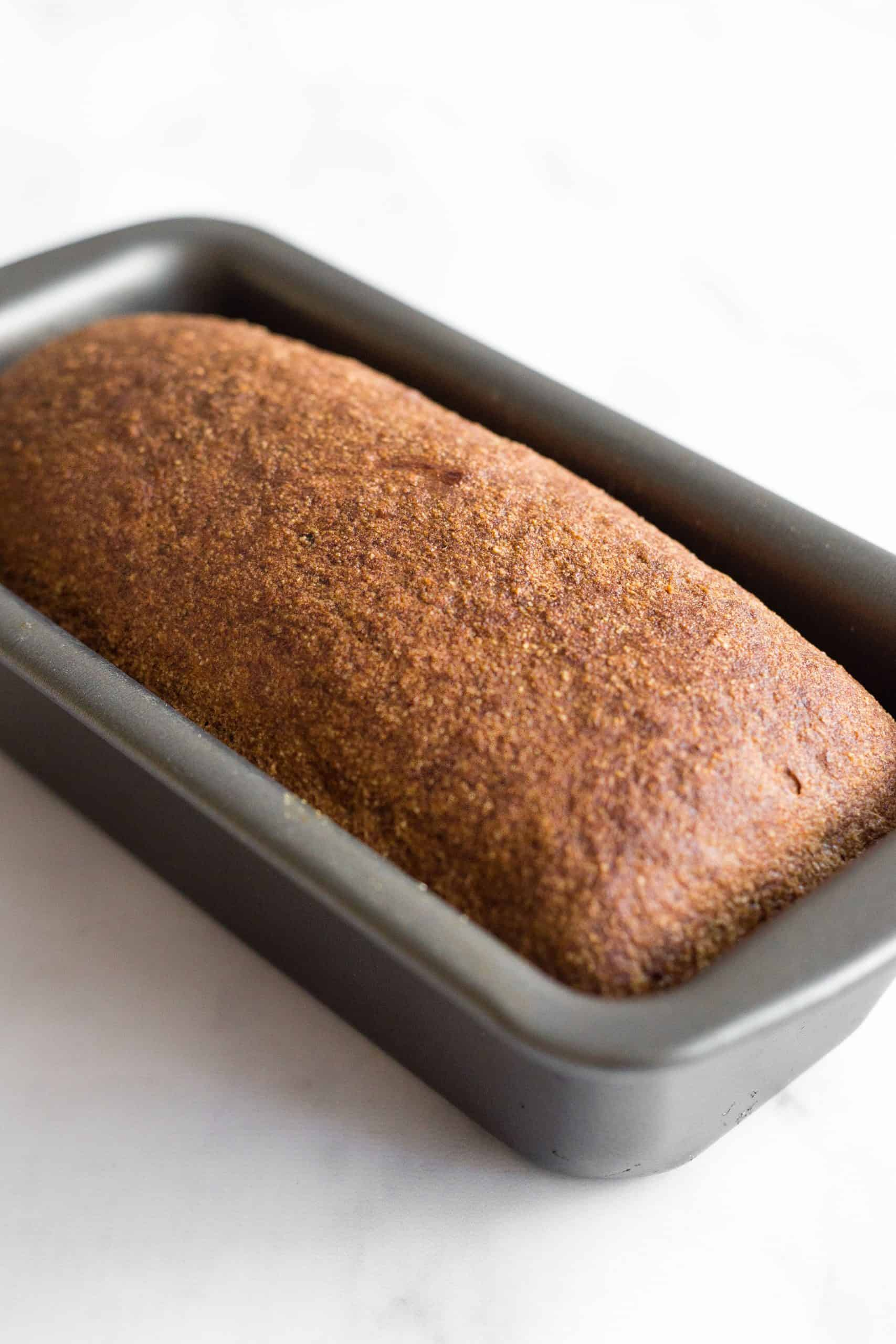 A just-baked loaf of brown bread in a metal pan.