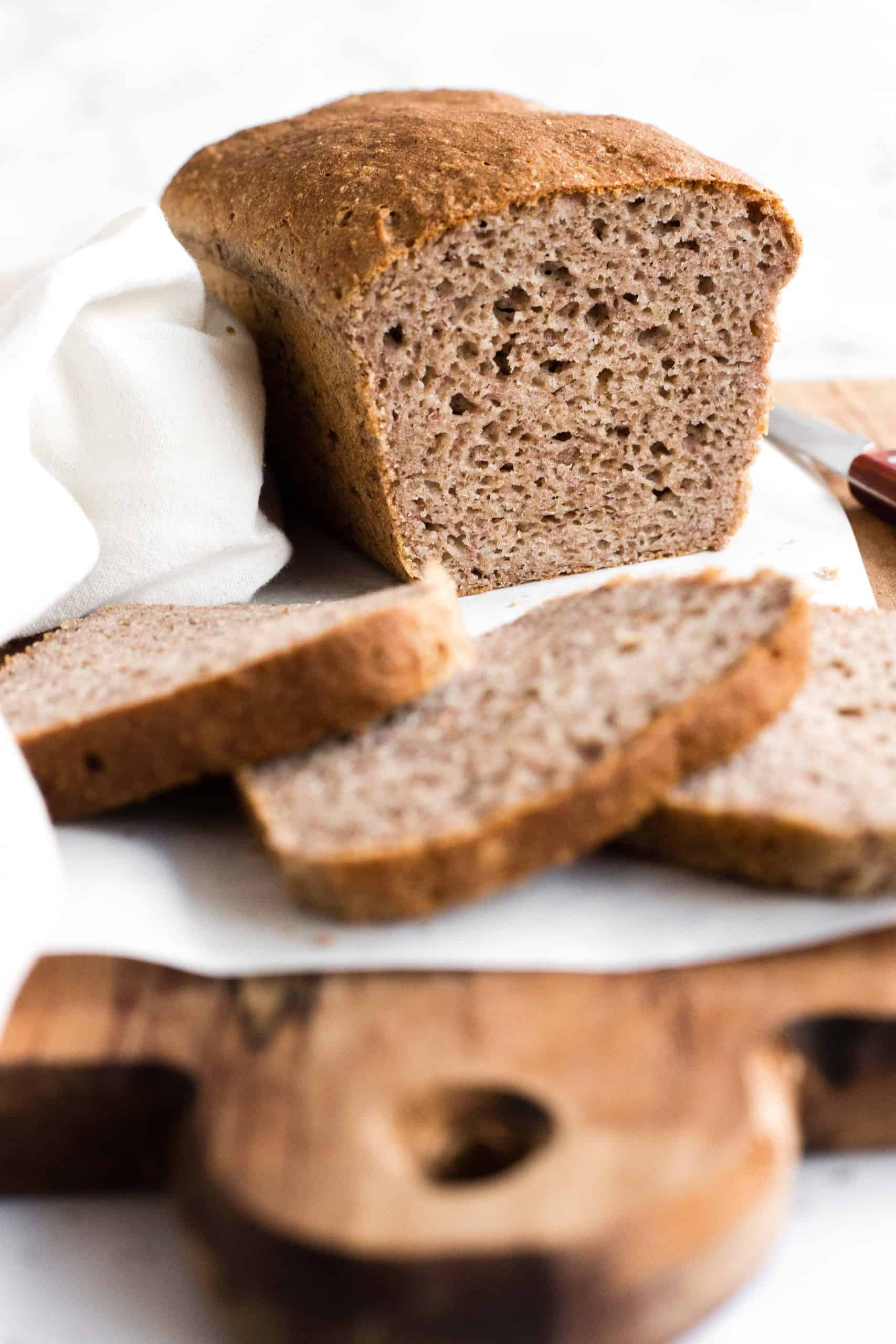 Sliced loaf of buckwheat bread on parchment-lined board.