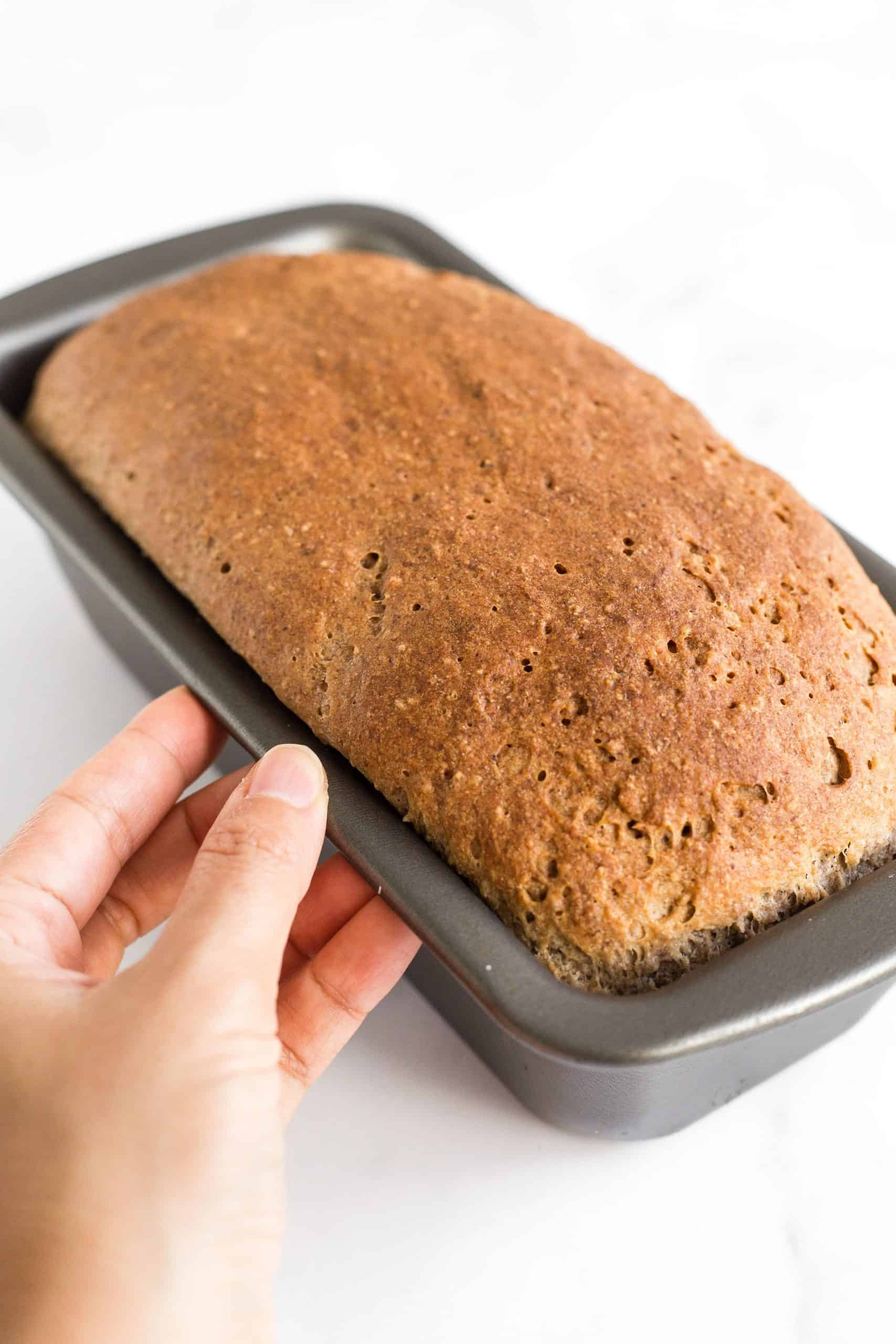 Holding a pan with a freshly baked loaf of bread.