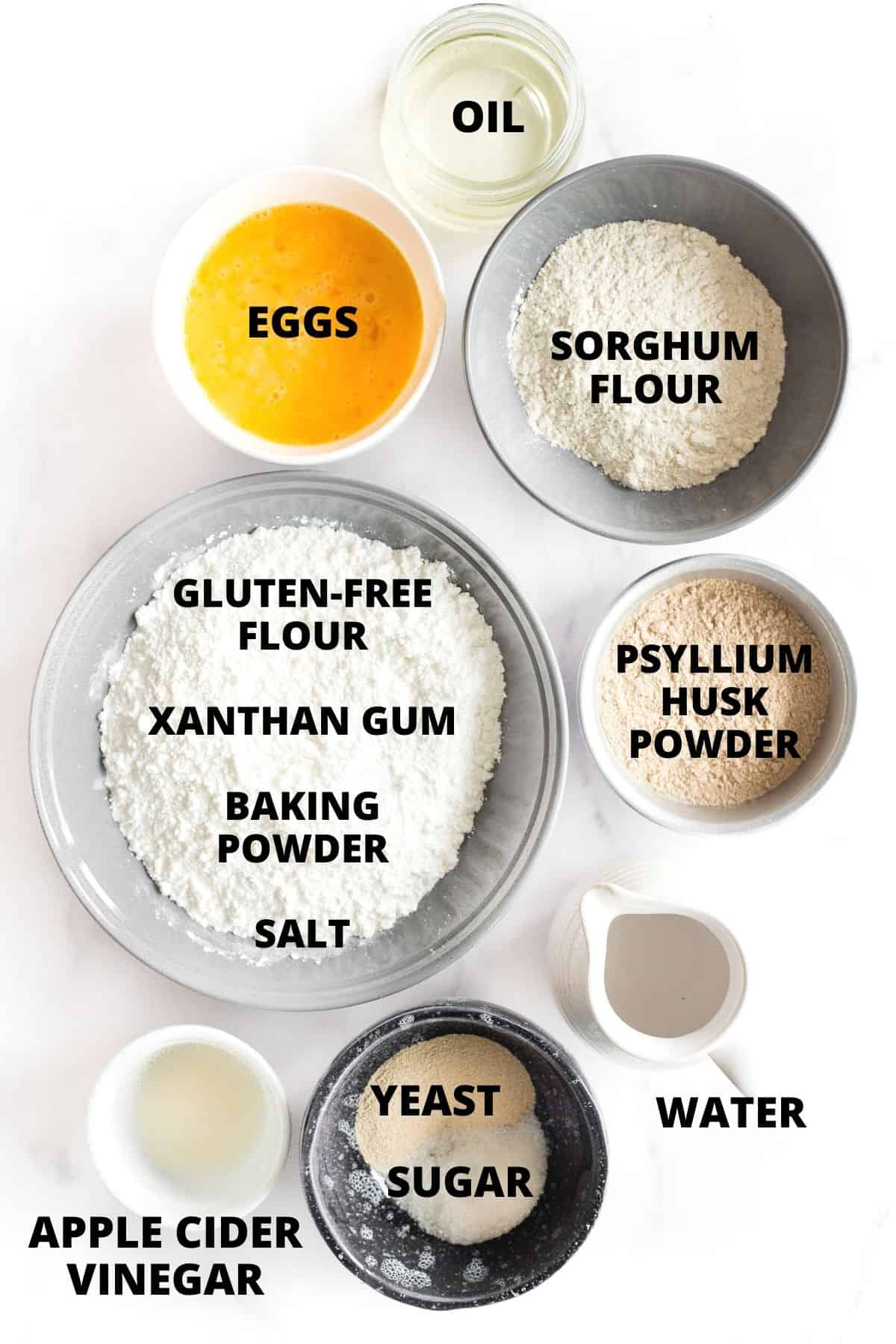 Labeled ingredients for making sorghum bread laid out on a marble board.