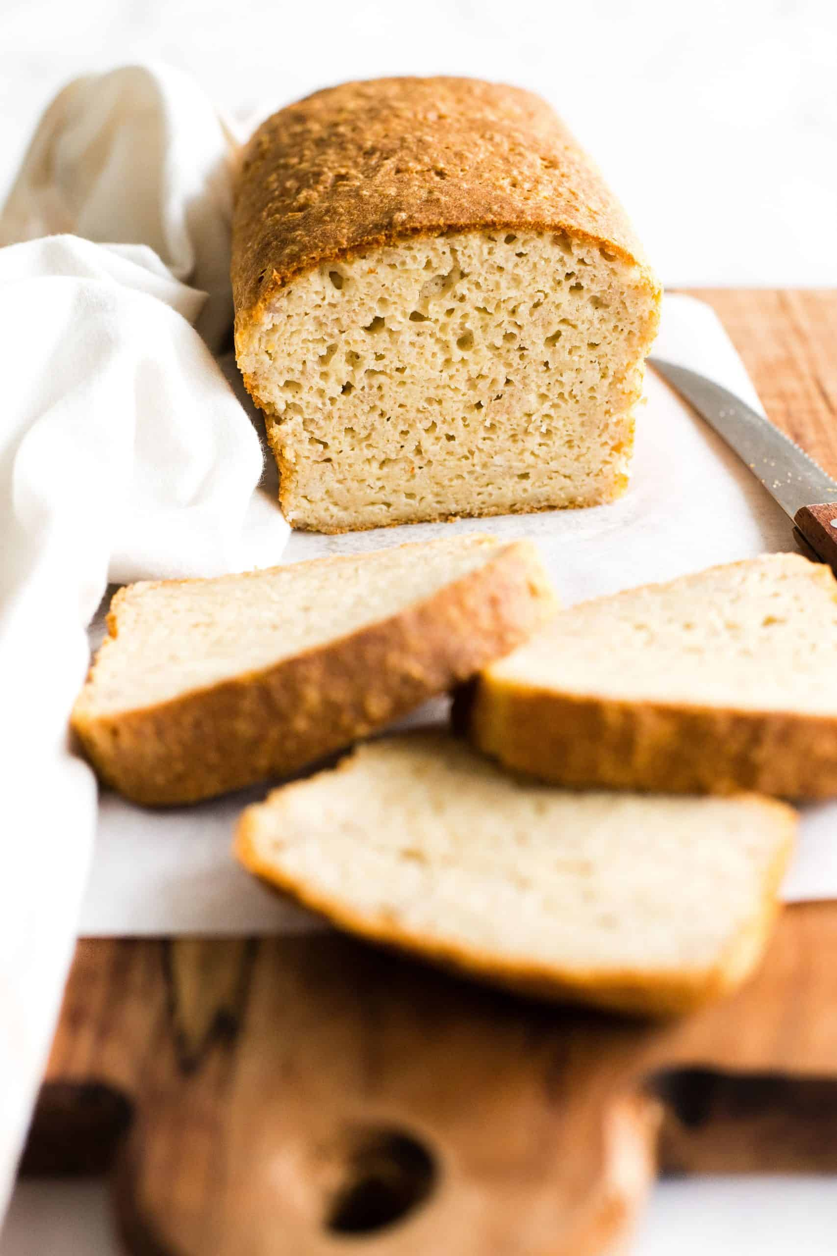 A half-sliced loaf of sorghum bread on a parchment-lined wooden board.