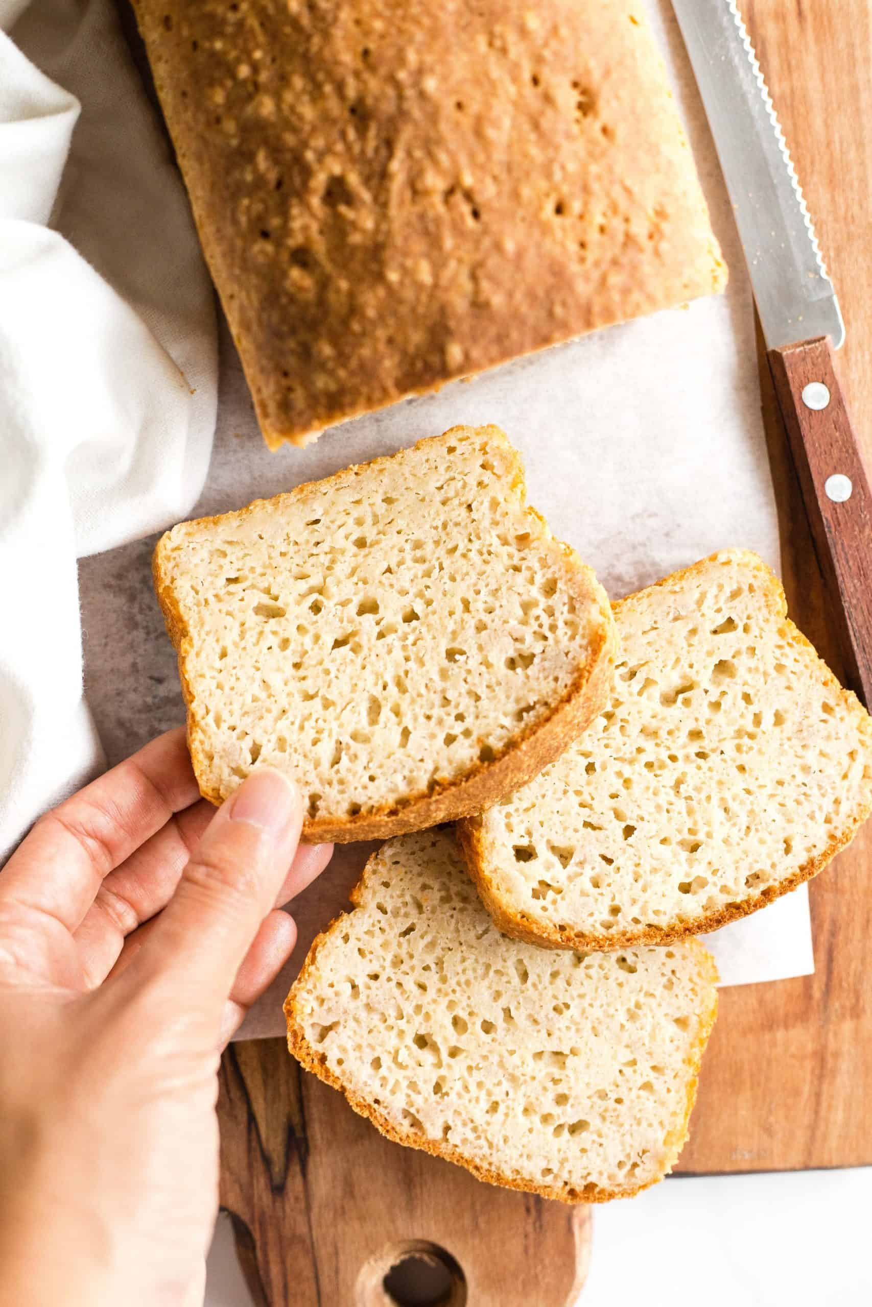 Hand reaching for a slice of bread.