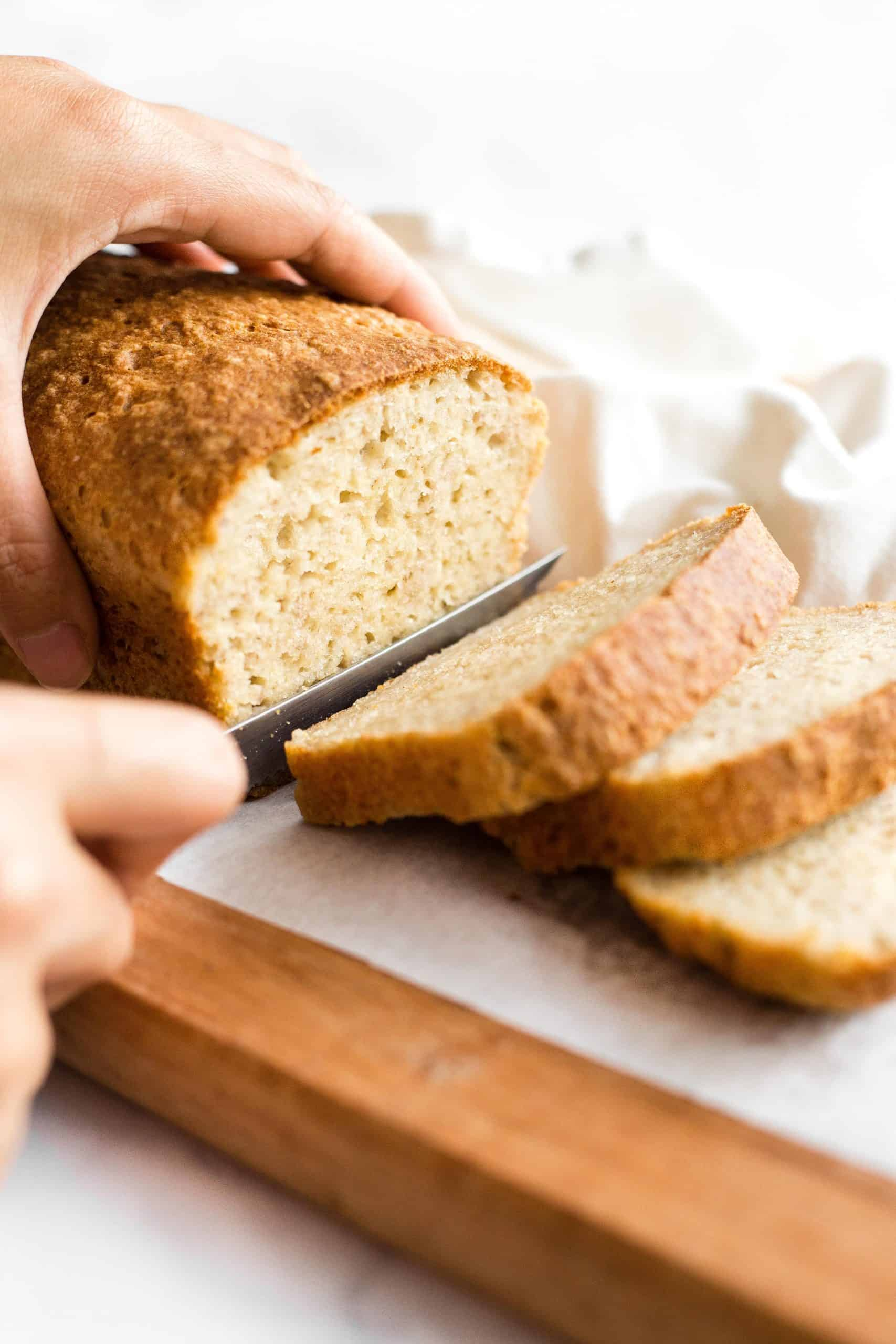 Hand slicing into a loaf of bread.