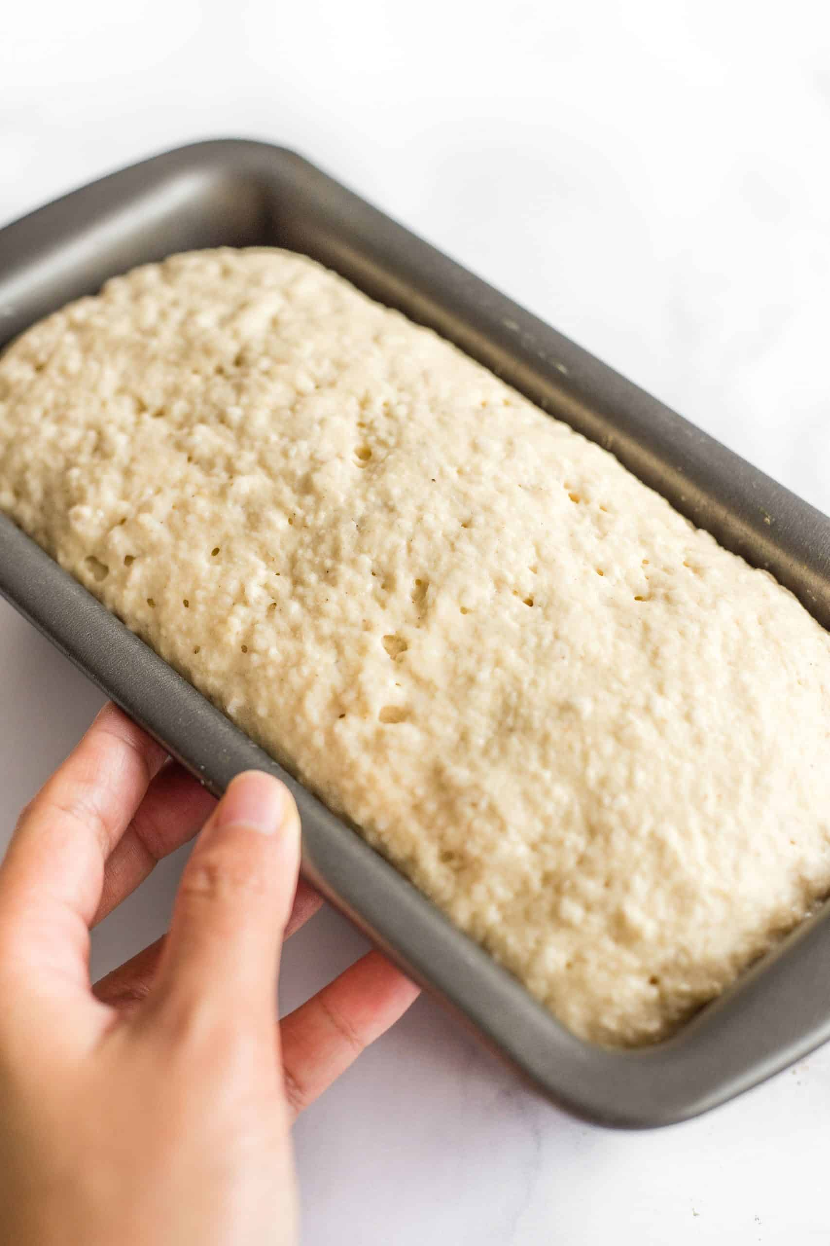 Hand holding a loaf pan with risen bread dough inside.