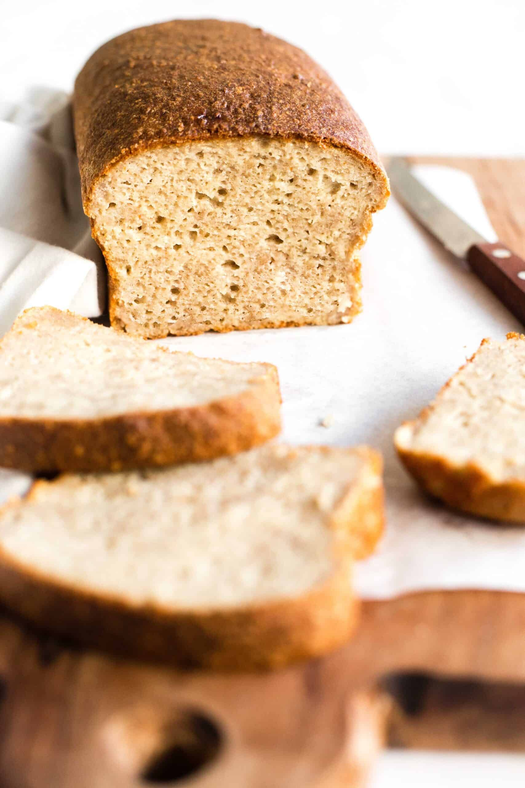A half-sliced loaf of yeast quinoa bread on a parchment-lined wooden board.