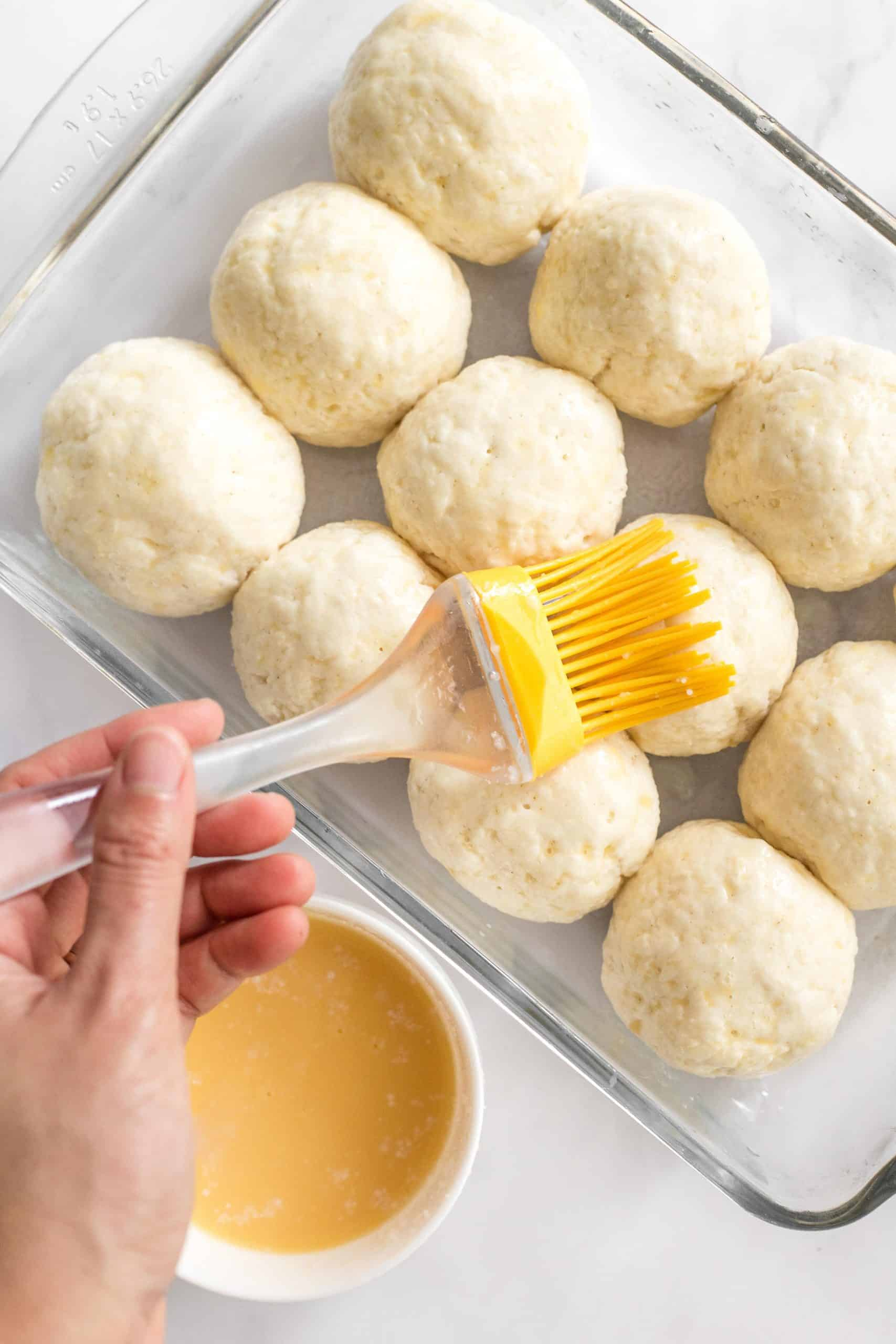 Hand brushing unbaked bread rolls with egg wash.