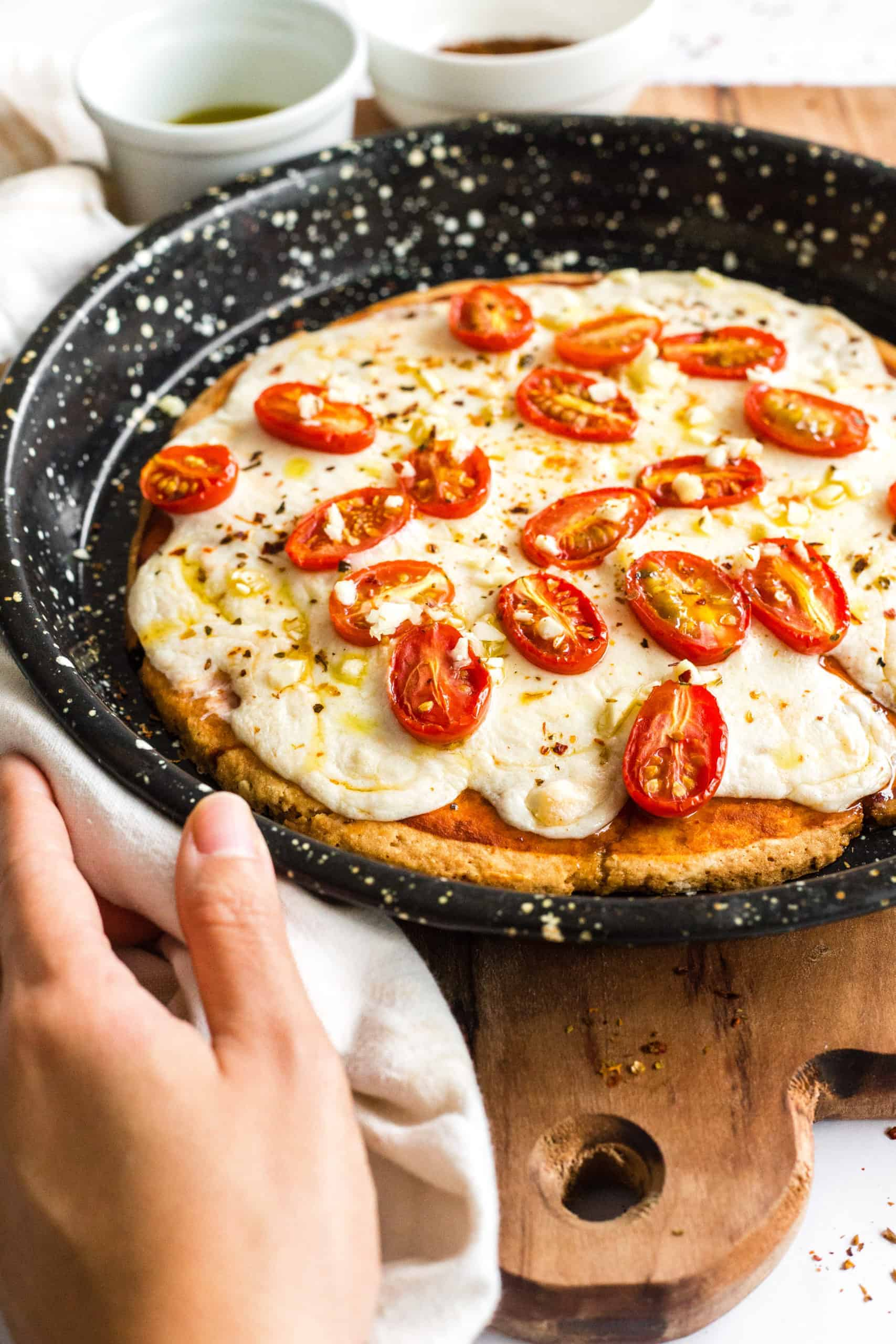 Gluten-free pizza in a pizza pan on a wooden board