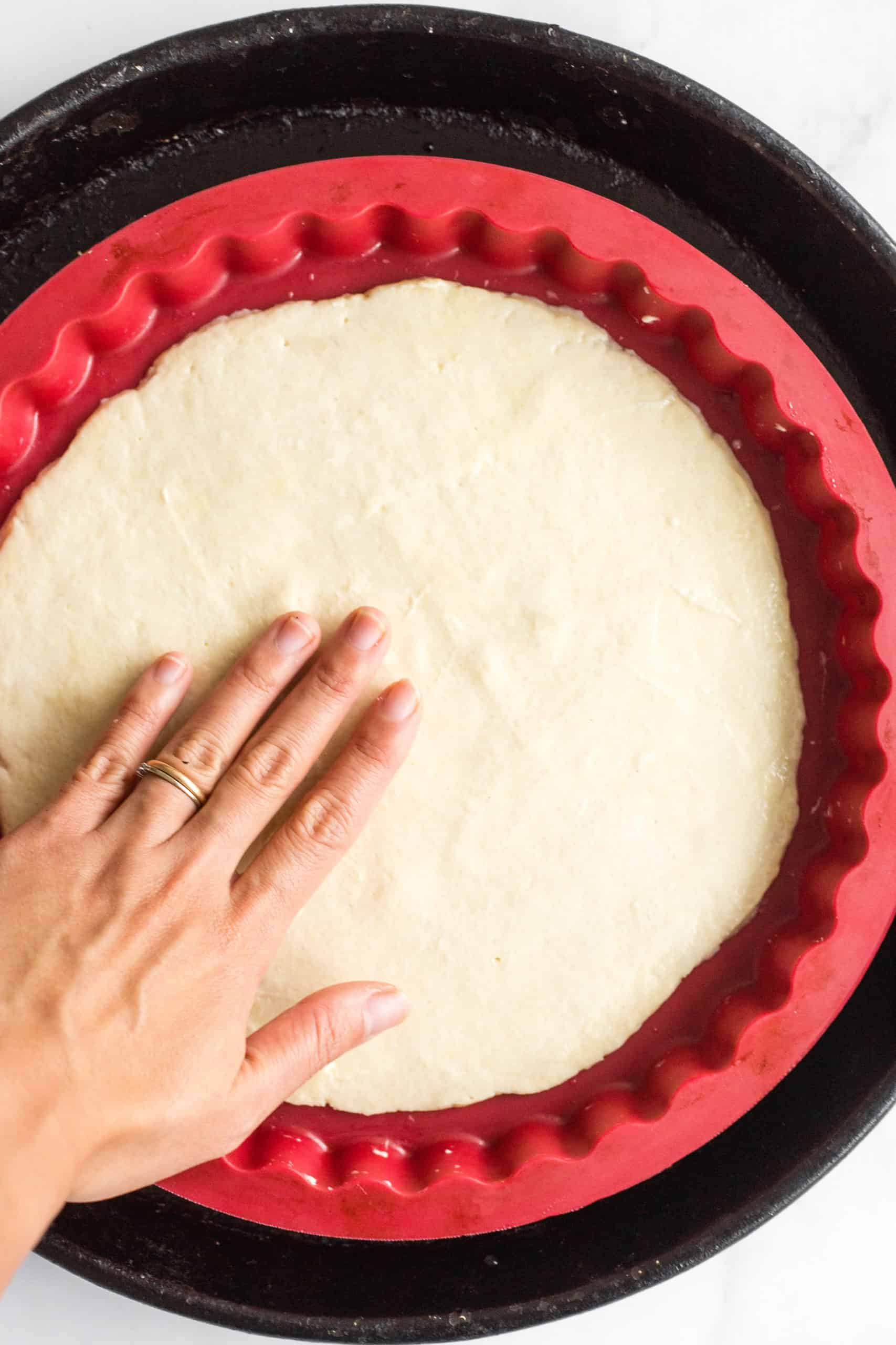 Spreading the gluten-free pizza dough on a silpat-lined pizza pan.