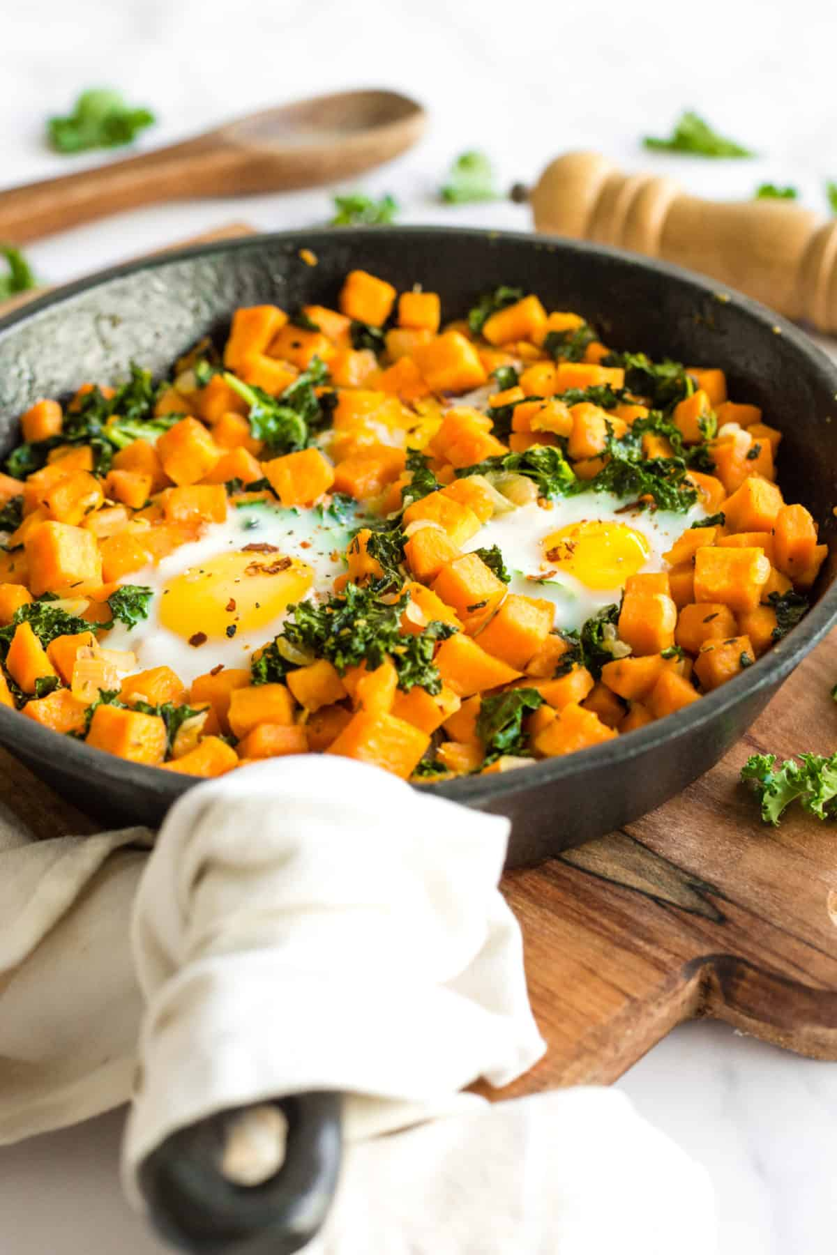 Sautéed sweet potato cubes and kale with eggs in a cast iron skillet.