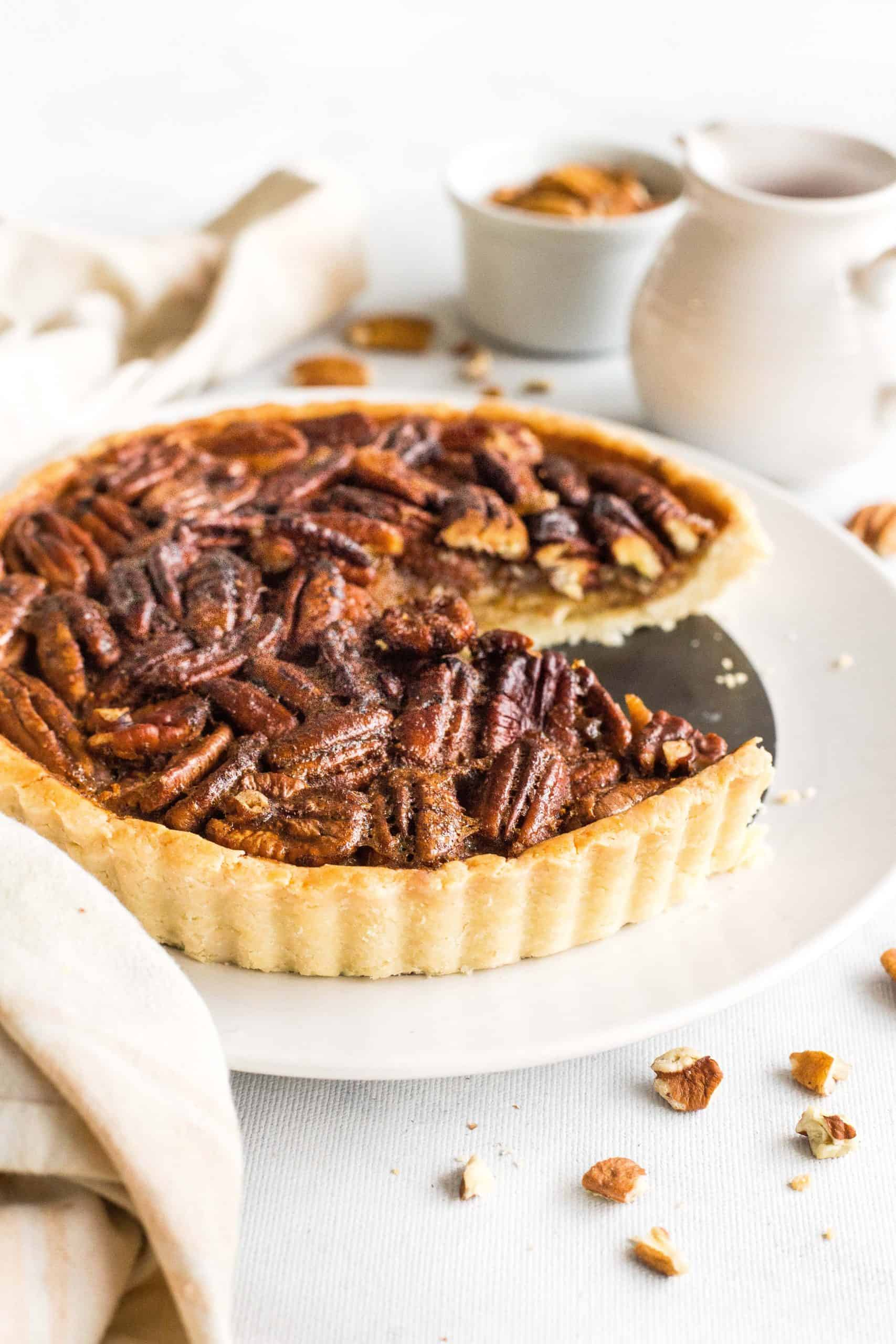 Sliced pecan pie on a white plate.