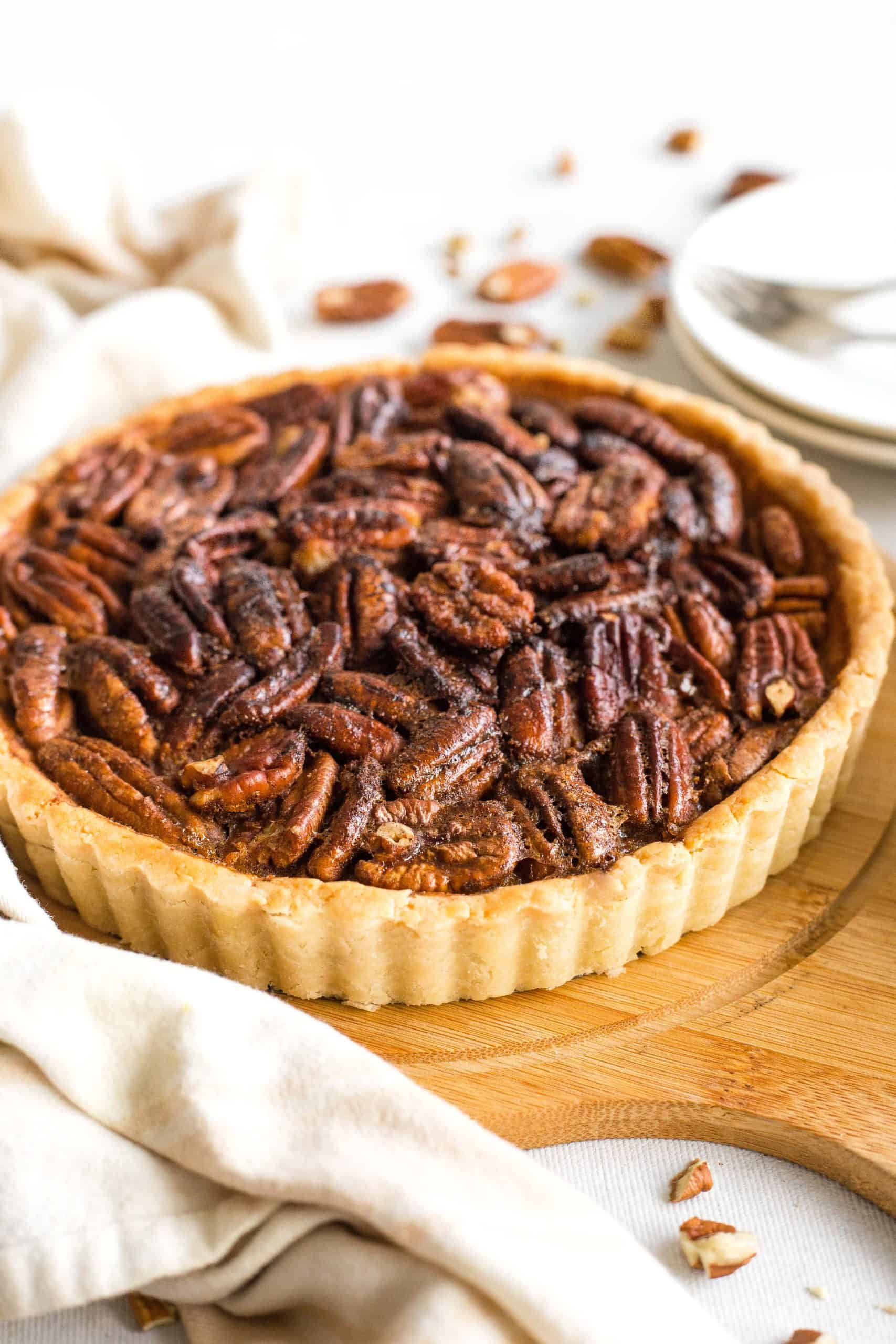 Whole pecan pie on a wooden board.