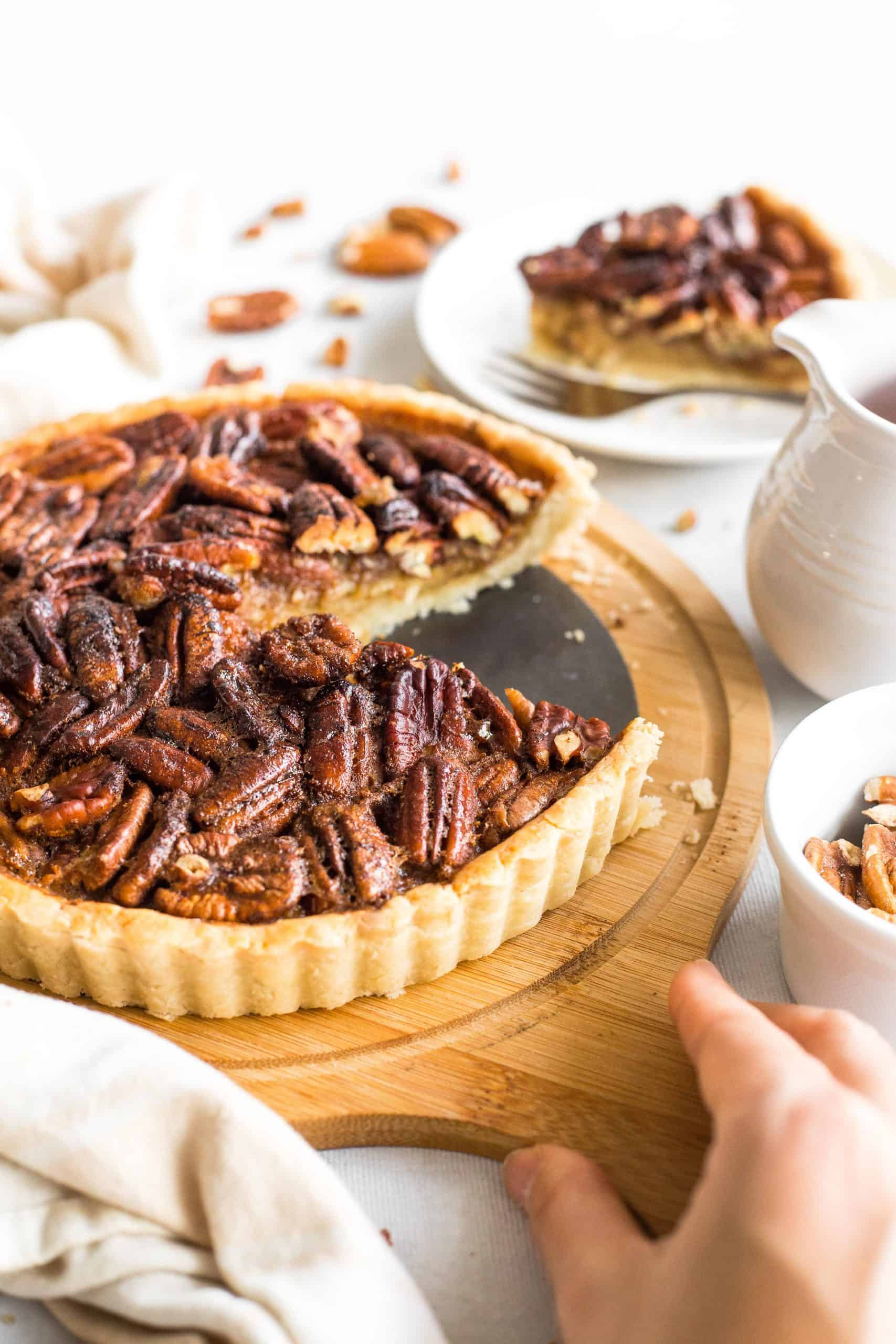 Hand holding a wooden board with pecan pie on it.