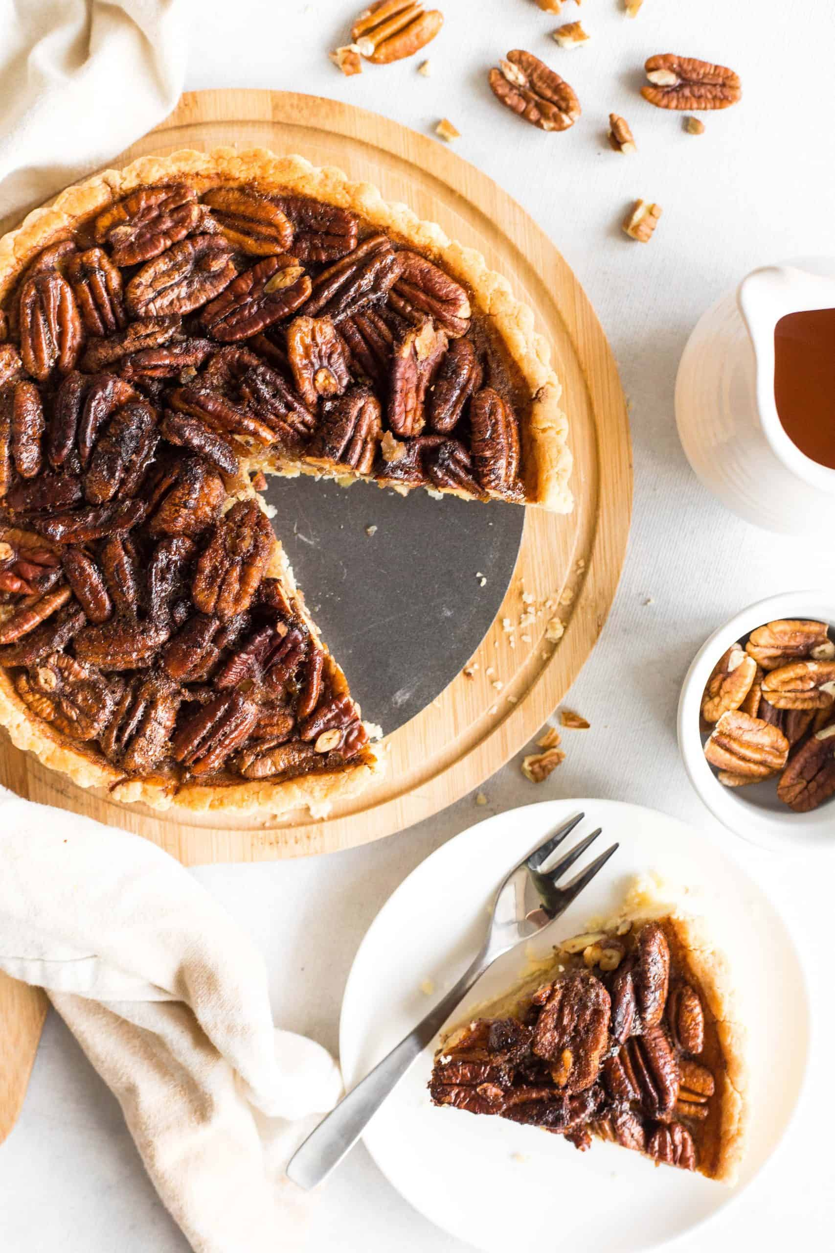 Whole pecan pie and a slice of pie on a white plate.