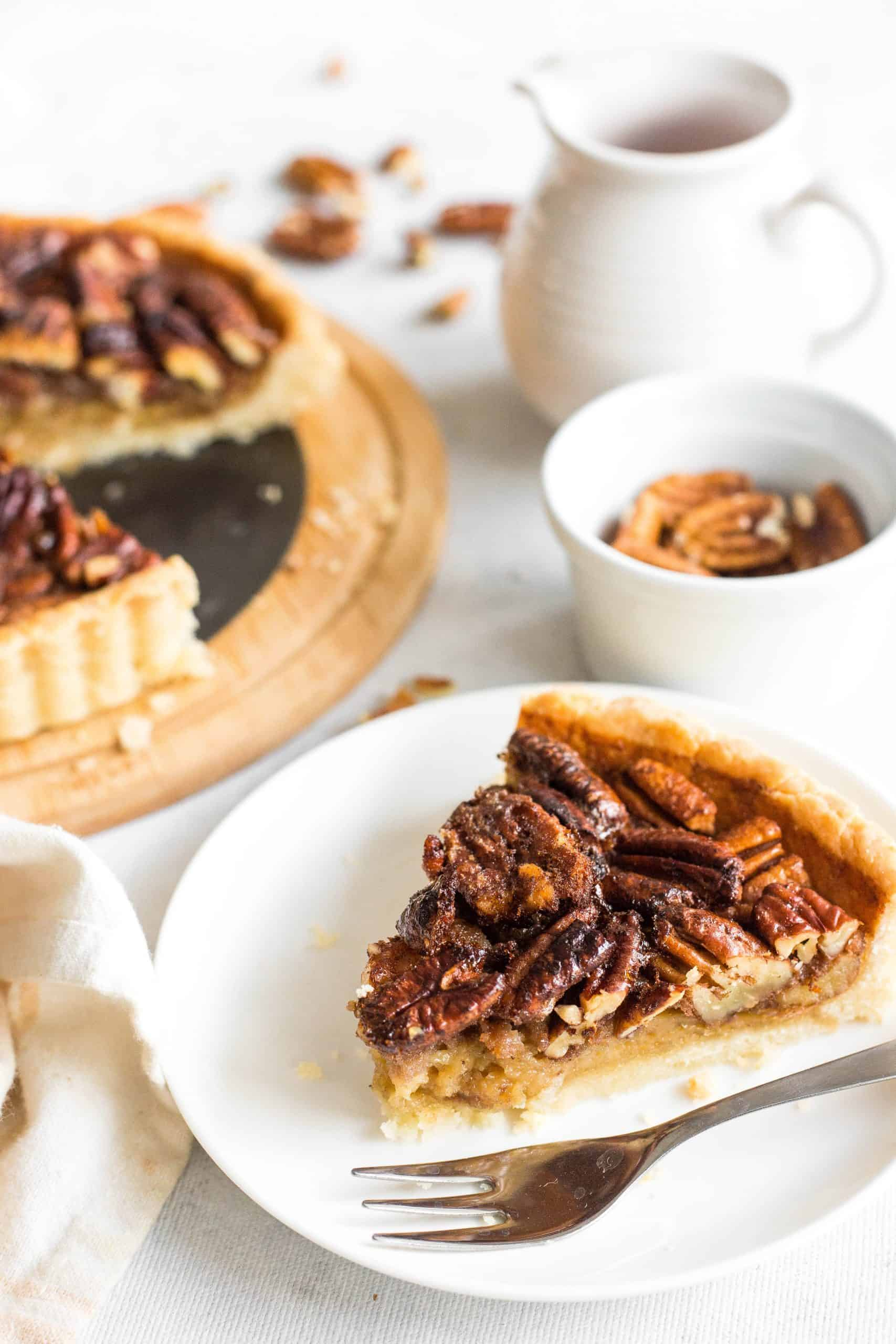A slice of pecan pie on a white placte.