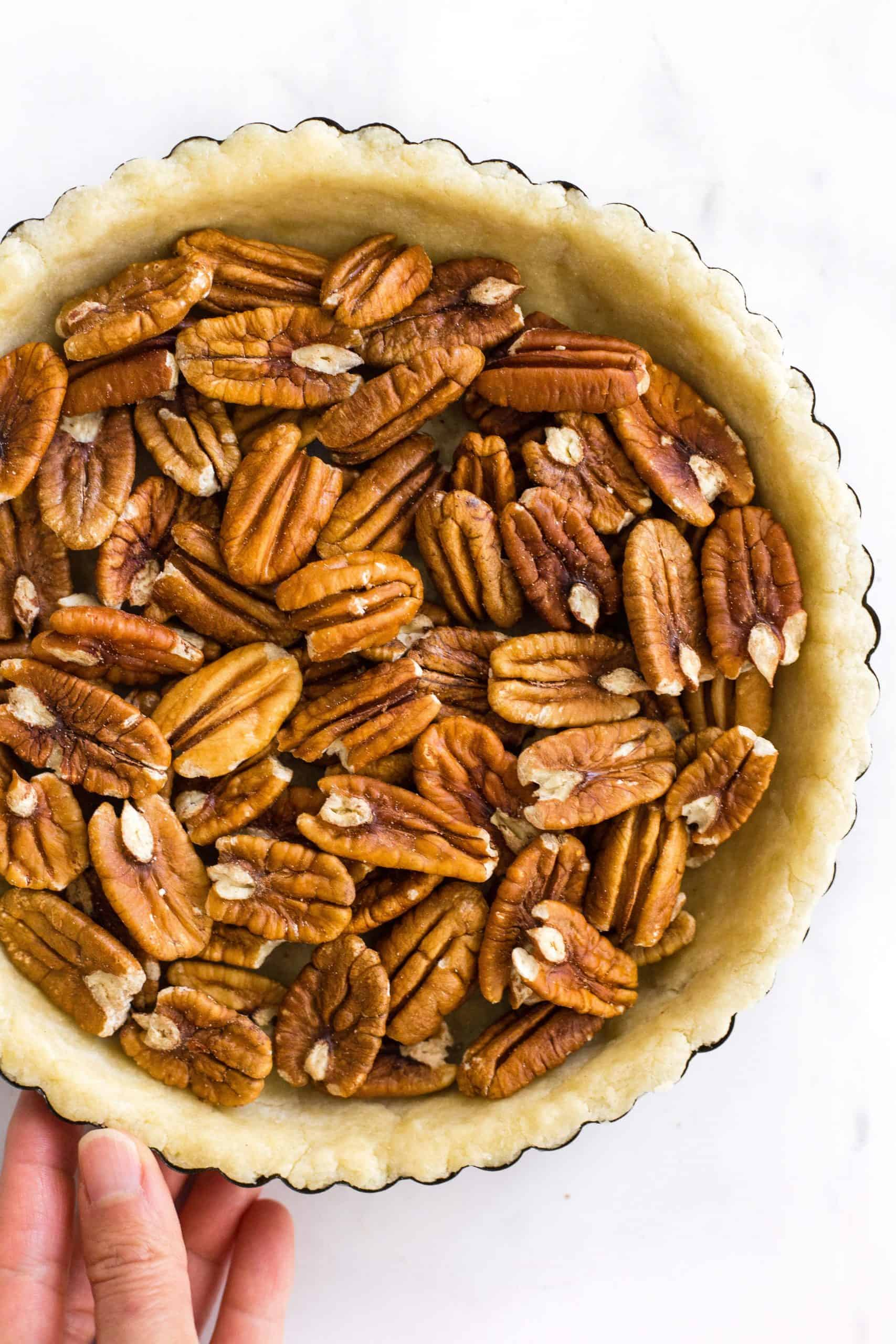Hand holding a pie tin with unbaked pie crust filled with pecans.