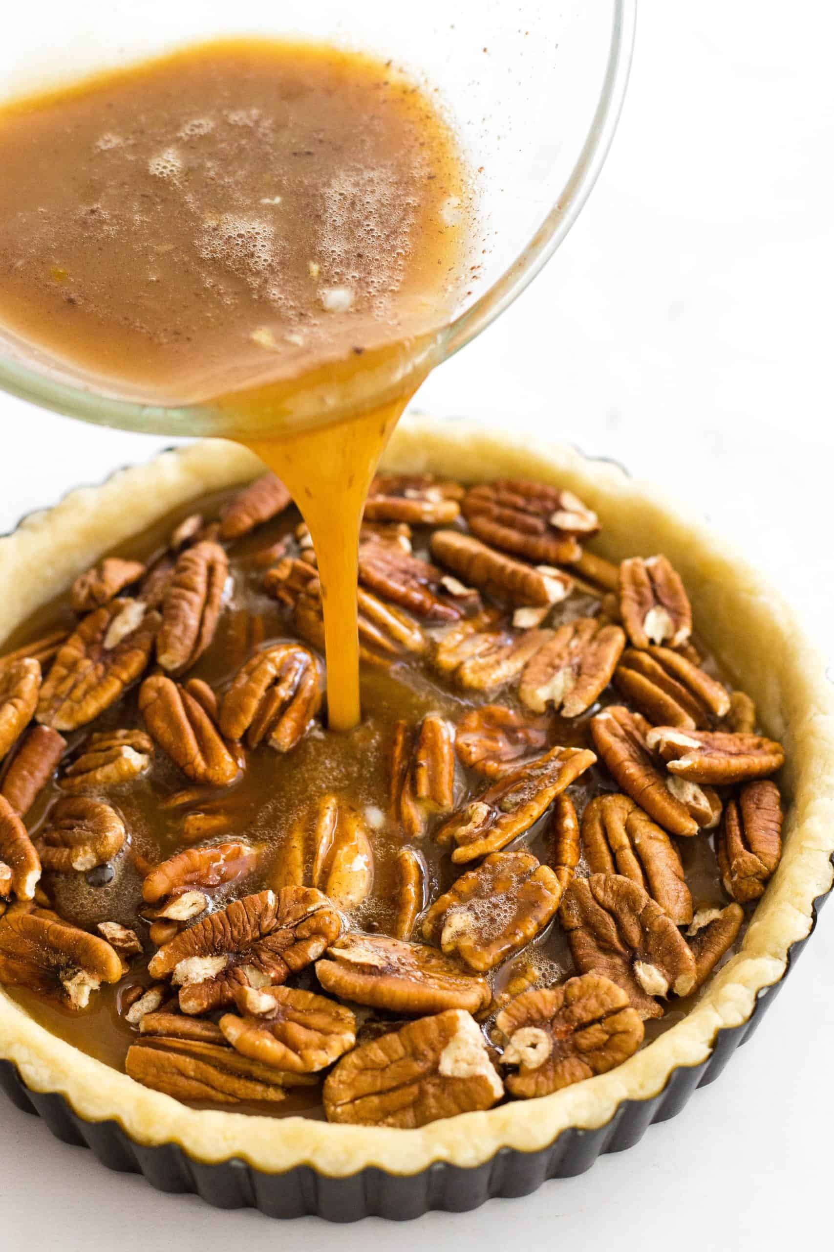 Pouring brown liquid into a crust filled with pecan nuts.