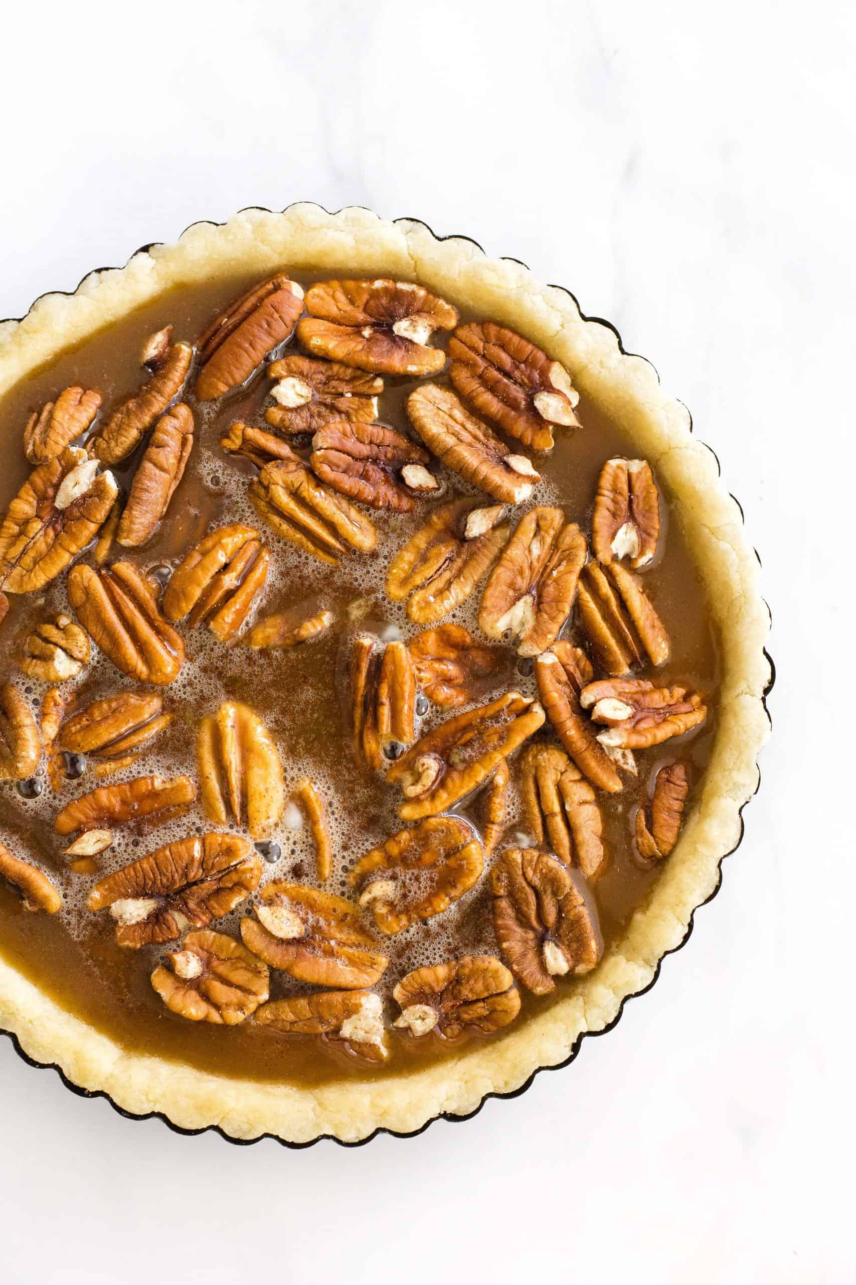 Uncooked pecan pie in a pie tin ready to be baked.