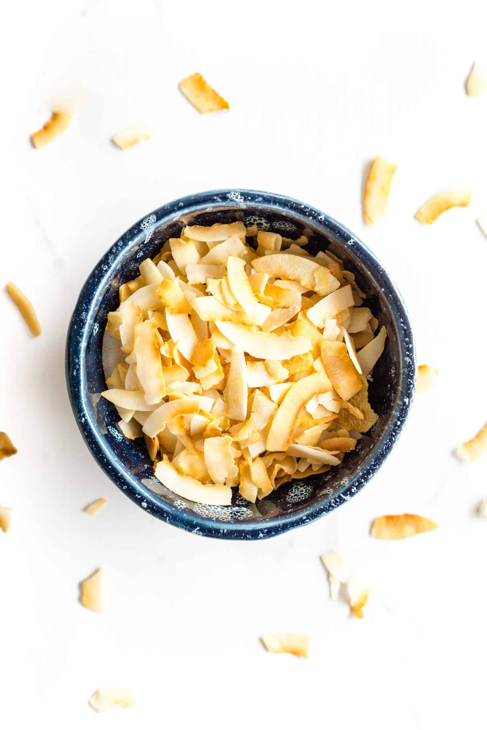 Maple coconut chips in a blue bowl on a marble board