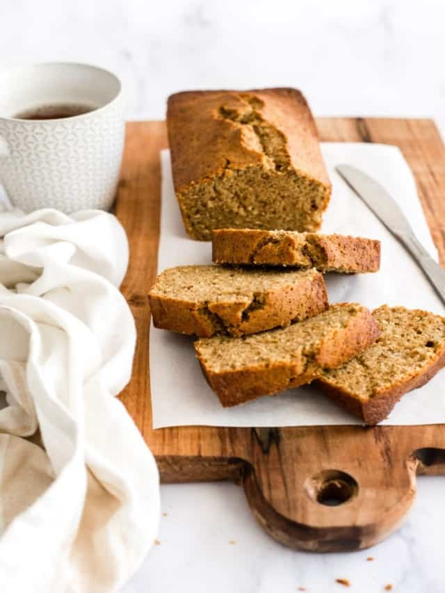 resized image of banana bread loaf and slices on a cutting board with cup of coffee and white towel