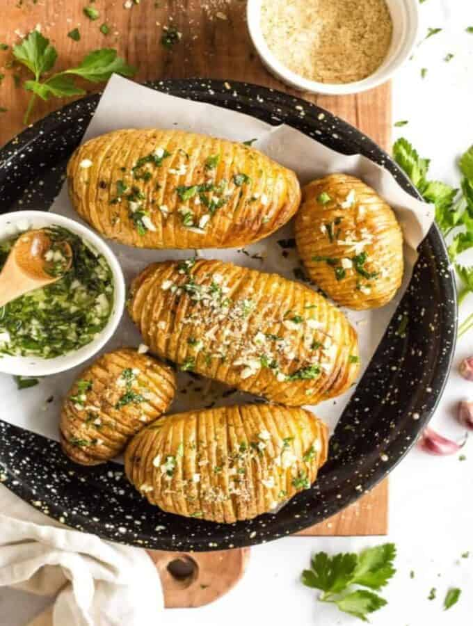 resized image of hasselback potatoes with parsley and garlic sauce on a black dish