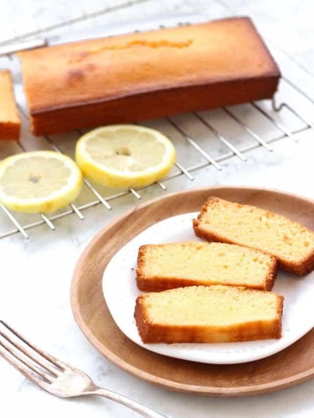 resized image of sliced lemon cake on white plate with cake and lemon slices on silver rack