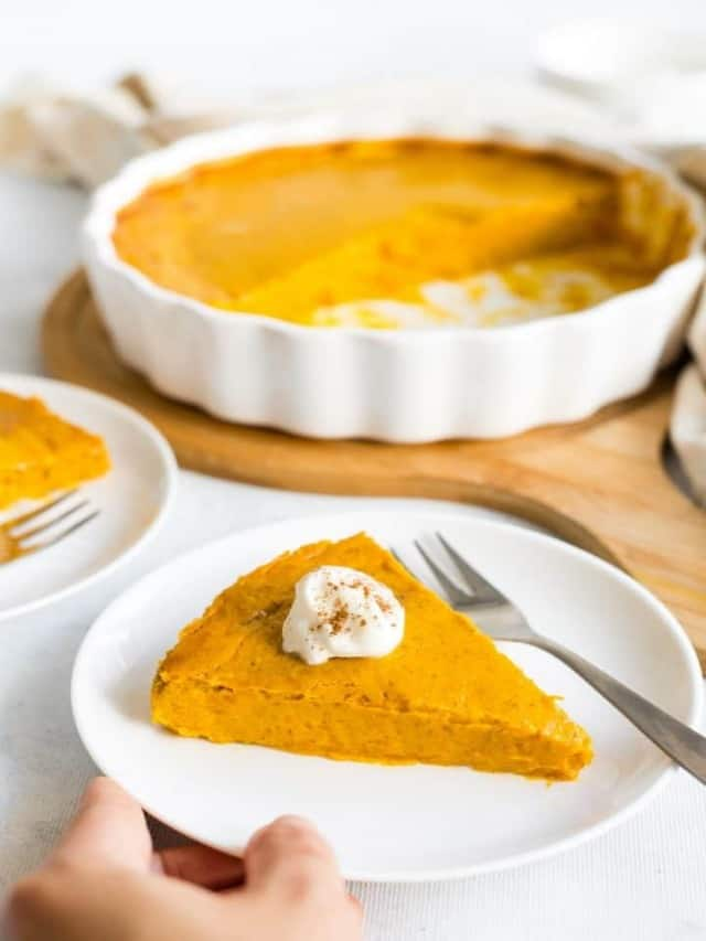 resized image of slice of pumpkin pie on white plate with dollop of whipped cream on top , pie in white ceramic pie dish on wood board